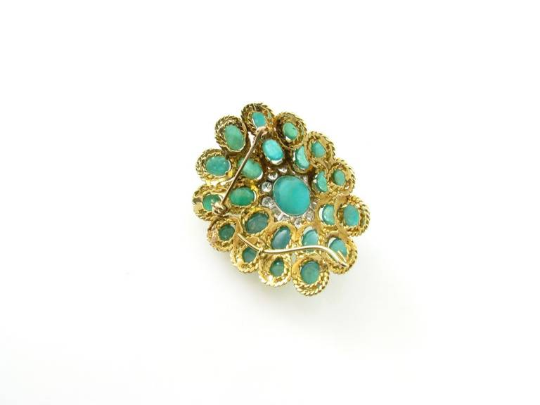 An 18 karat yellow gold emerald and diamond brooch with pendant attachment, Circa 1960s.  The brooch is of oval bombe form set with 23 oval cabochon emeralds weighing a total of approximately 23.60 carats, the center emerald set within a round