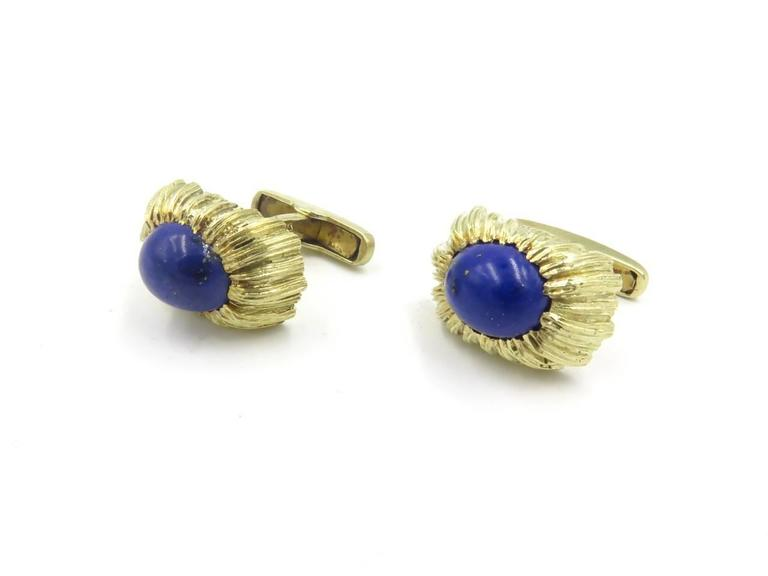 A pair of 14 karat yellow gold and lapis lazuli cufflinks. Each single link centering an oval cabochon lapis lazuli, measuring approximately 12.00 x 10.00mm, within a regular fluted and textured surround, joined by a bar to a swivel link. Length is