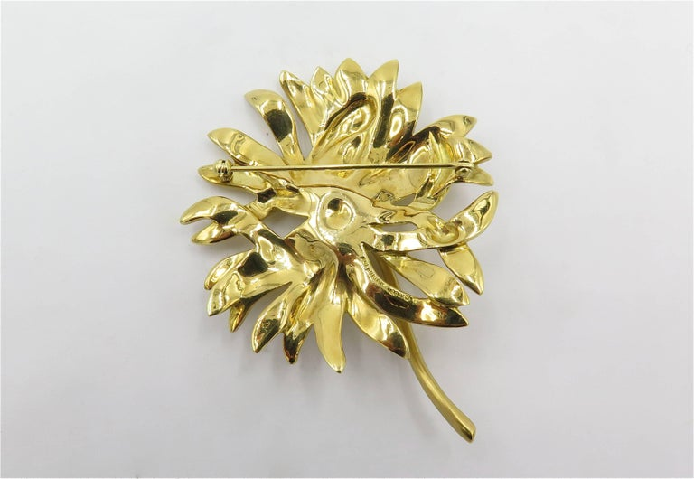An 18 karat yellow gold brooch. Angela Cummings. Designed as a textured gold reverse textured gold chrysanthemum, with polished gold stem. Length is approximately 2 3/4 inches. Gross weight is approximately 36.4 grams. Stamped Cummings 18K, 1989.