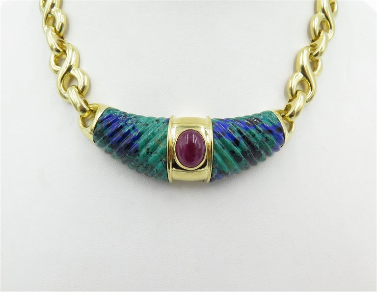 An 18 karat yellow gold, azurmalachite and ruby necklace. David Webb. Circa 1990.  Centering a caved azurmalachite panel, centering an oval cabochon ruby, suspended from a polished figure 8 link chain. Length is approximately 14 inches.  Gross