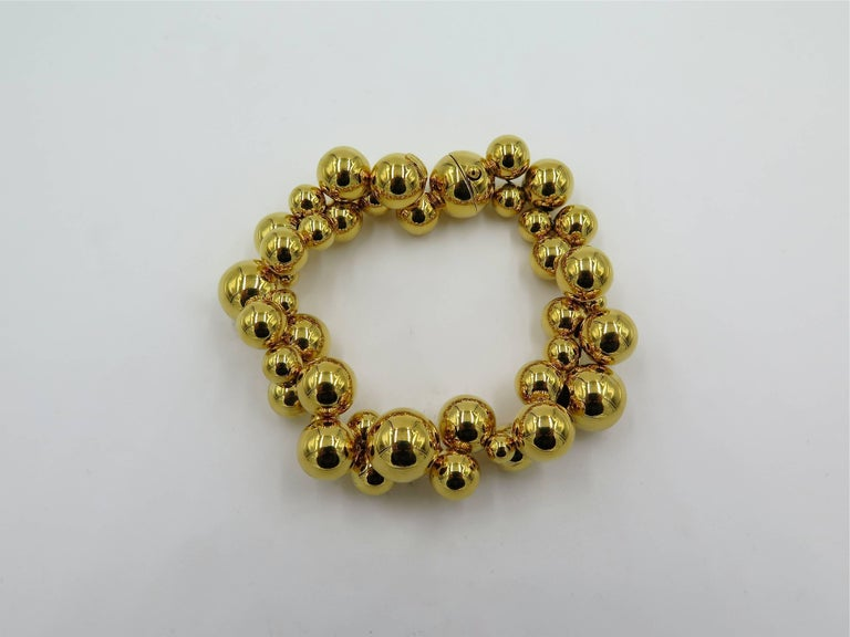 An 18 karat yellow gold Atomo bracelet. Marina B. Designed as a strand of variously sized polished gold beads. Length is approximately 7 1/2 inches. Gross weight is approximately 50.0 grams. With signed pouch. Stamped Marina B. Numbered 585001.