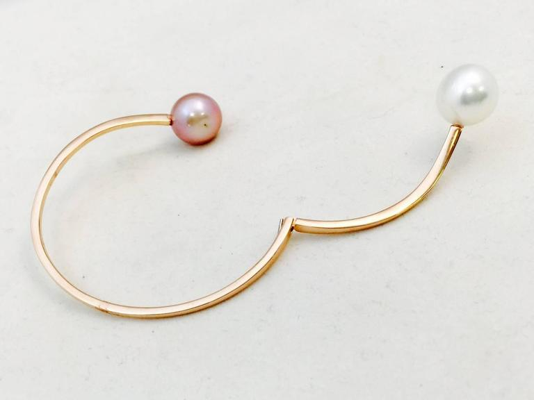 Elegance in simplicity.  Crafted in wildly popular 18 karat rose gold featuring 13-14MM pearls.  The natural pink cultured Freshwater pearl enhances the rose gold and the white cultured South Sea pearl is simply classic.  Hinged for ease of wear.  A