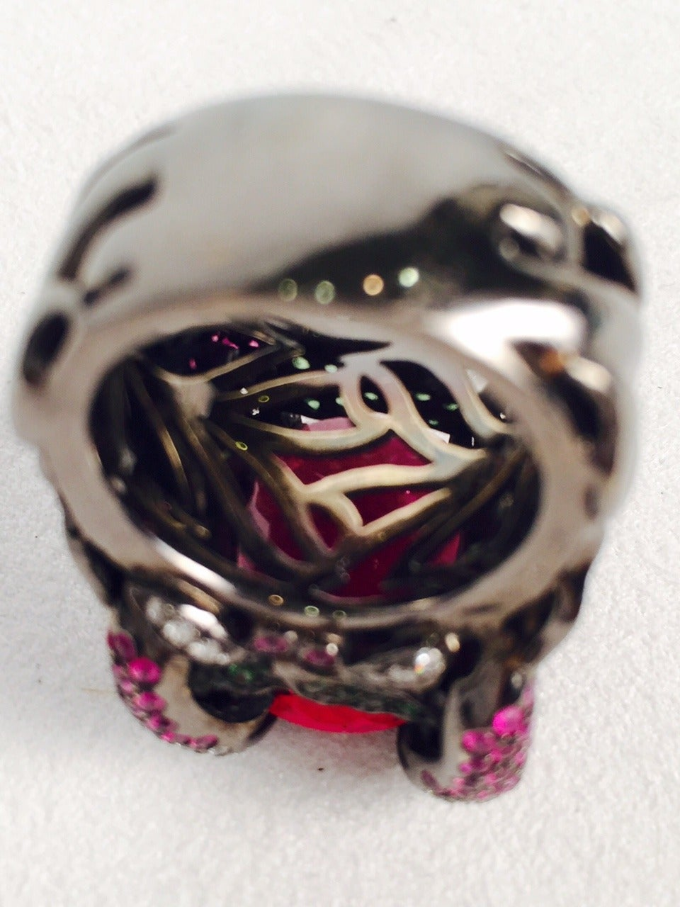 18K blackened gold featuring an oval Rubellite Tourmaline weighing approximately 15 carats, artfully held in place with 4 snake prongs sprinkled with brilliant cut diamonds weighing approximately 1.00 carat.  Sides enhanced with leaves in green