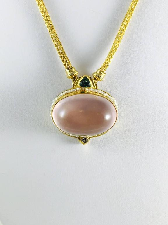 Unusual and stunning necklace!  22K yellow gold Wheat Chain holds a fabulous oval, bezel set, cabochon pink quartz surrounded by tiny seed pearls in a custom created 24K yellow gold frame.  Atop the frame sits a bezel set trillion green tourmaline.