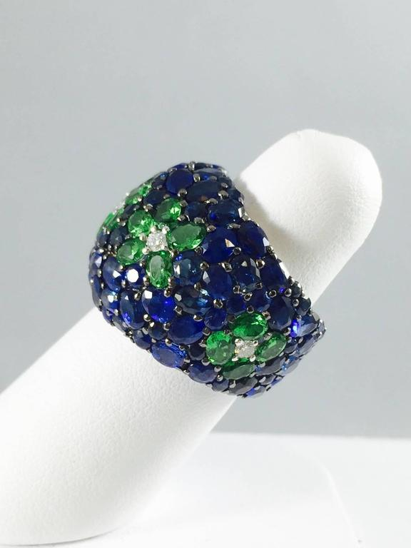 Prepare to be dazzled!  Meticulously crafted in 18 Karat White Gold one finds a sea of round and oval faceted Blue Sapphires.  Five flower patterns comprised of faceted Green Tsavorites with brilliant cut diamond centers. Stones are set with shared