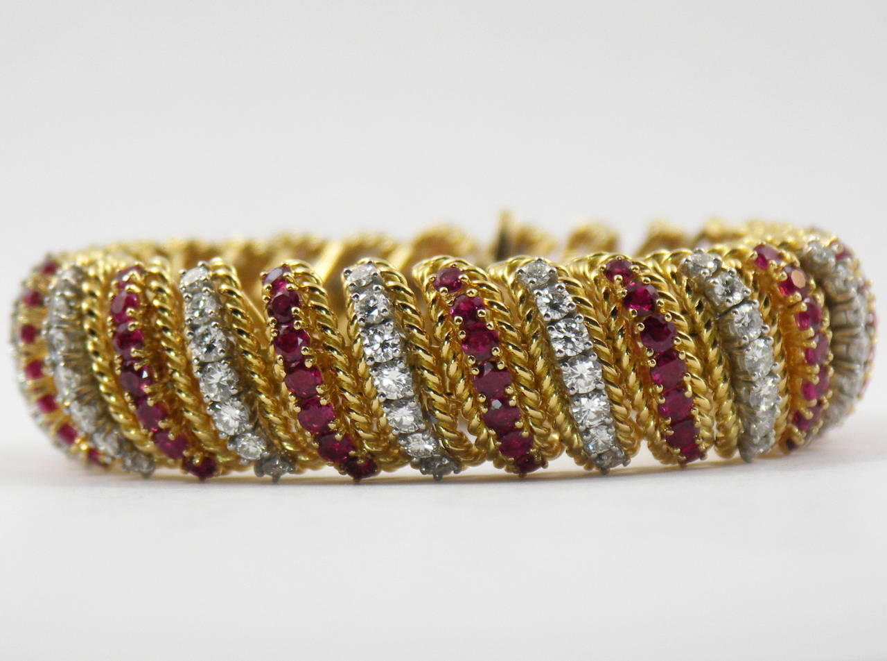 An 18K yellow gold bracelet, of rope design, and comprised of alternating links of rubies and diamonds. There are 112 diamonds weighing a total of approximately 9ct total weight, and 98 rubies weighing approximately 10.75 ct total weight. Weight 136
