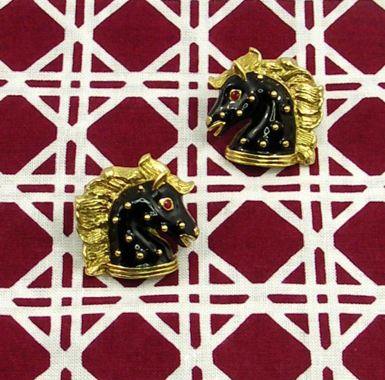 A pair of ladies 18K yellow gold equestrian themed earrings by Hidalgo. Measuring just over an inch square, they are beautifully enameled in black with red eyes, and flowing manes. Weight 20 grams.
