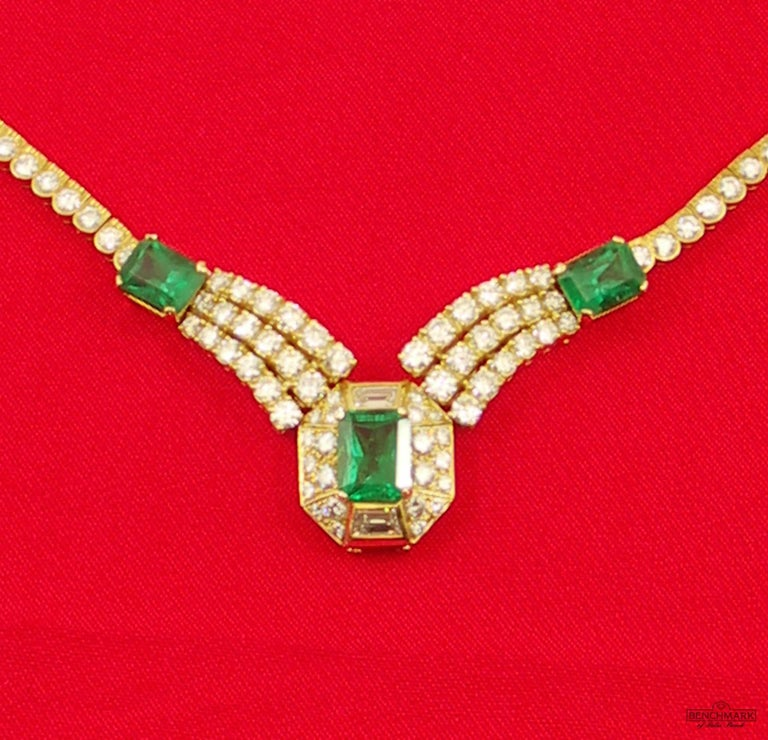 An 18 karat yellow gold necklace, centered around an emerald cut emerald weighing 3.38ct, as described in A.G.L. certificate #1088611, as being of Zambian origin, and absent of enhancements. Surrounded by 22 round brilliant cut diamonds weighing