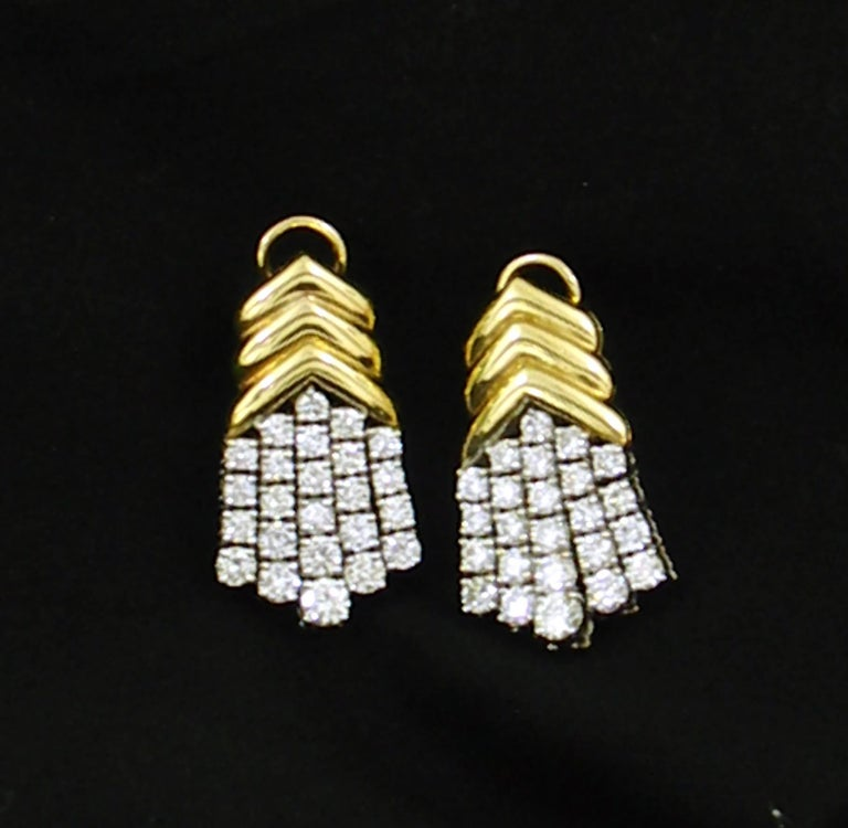 A pair of ladies 18K yellow and white gold earrings comprised of a yellow gold top comprised of three chevrons, and a bottom with five tassels of diamonds set in white gold. Each earring is set with 24 round brilliant cut diamonds for a total of 48