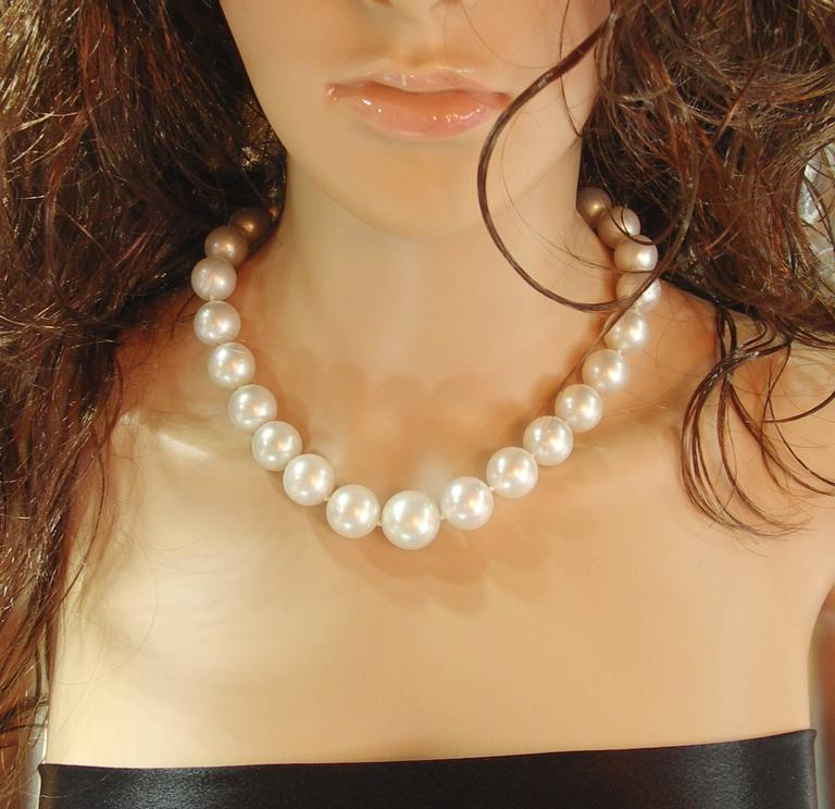 One Choker length strand of South Sea pearls, graduating from 14mm up to 18mm, of white bodycolor, and pink overtone. Luster is Very Good, and the surface has light to moderate spotting. The necklace is nicely finished with a platinum clasp set with