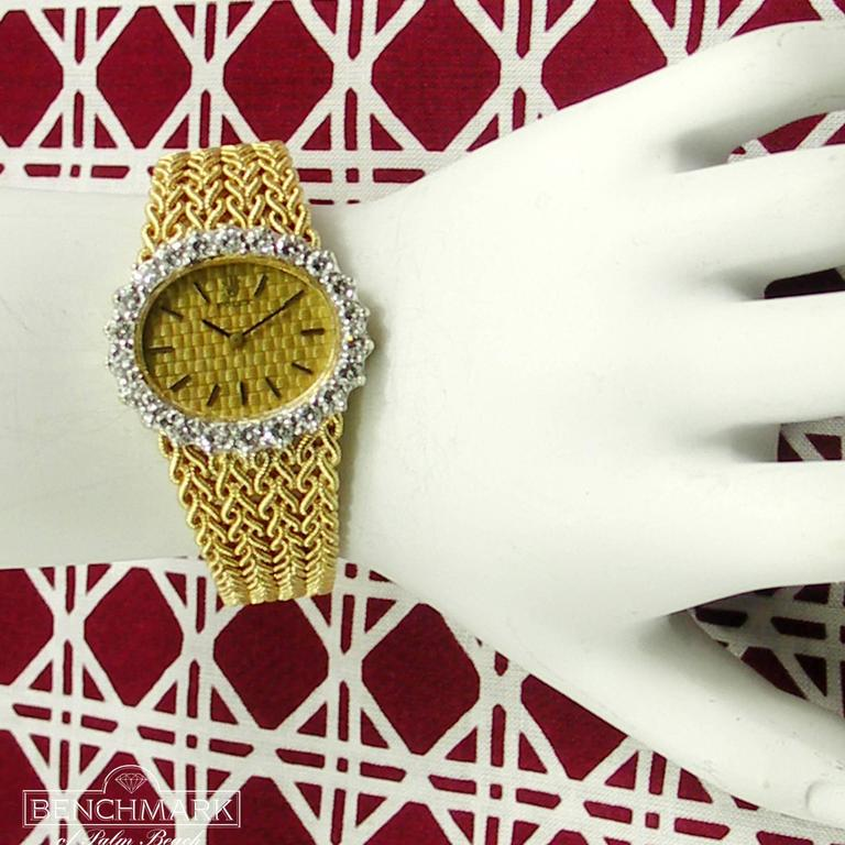 Rolex lady's 18k yellow gold and diamond bracelet watch with manual-wind movement, quilted, champagne dial. The oval watch head has a diamond bezel set with 22 round brilliant-cut diamonds weighing an approximate total of 2.50cts of overall G color