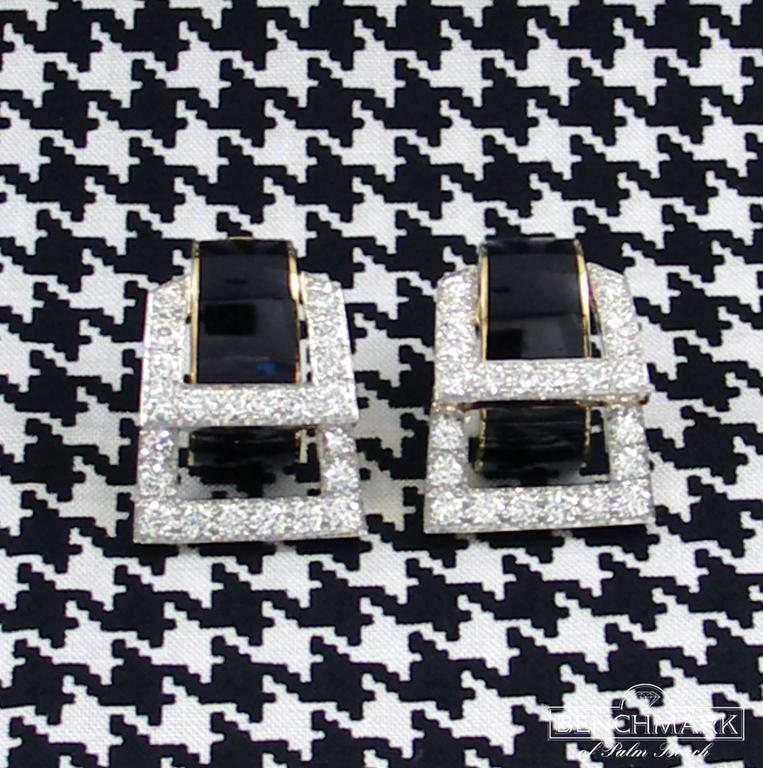 Fabulous buckle style David Webb 18K Yellow Gold and Platinum earrings, set with 48 diamonds weighing an approximate total of 7.00CT of overall F/G Color and VS1 Clarity. The black enamel centers are striking against the diamond buckles. Clip on