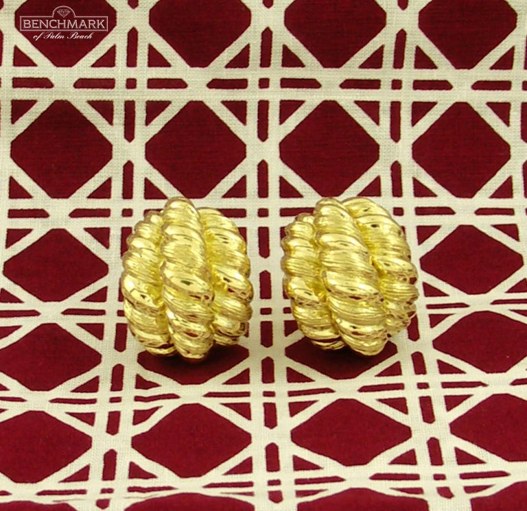 A pair of ladies, 18 karat yellow gold earrings measuring 7/8 of an inch wide, and 1 1/8 inch long, comprised of 3 rows of twisted rope design. With a bombe' front, they have an excellent scale and dimension. These fashionable mid-century earrings