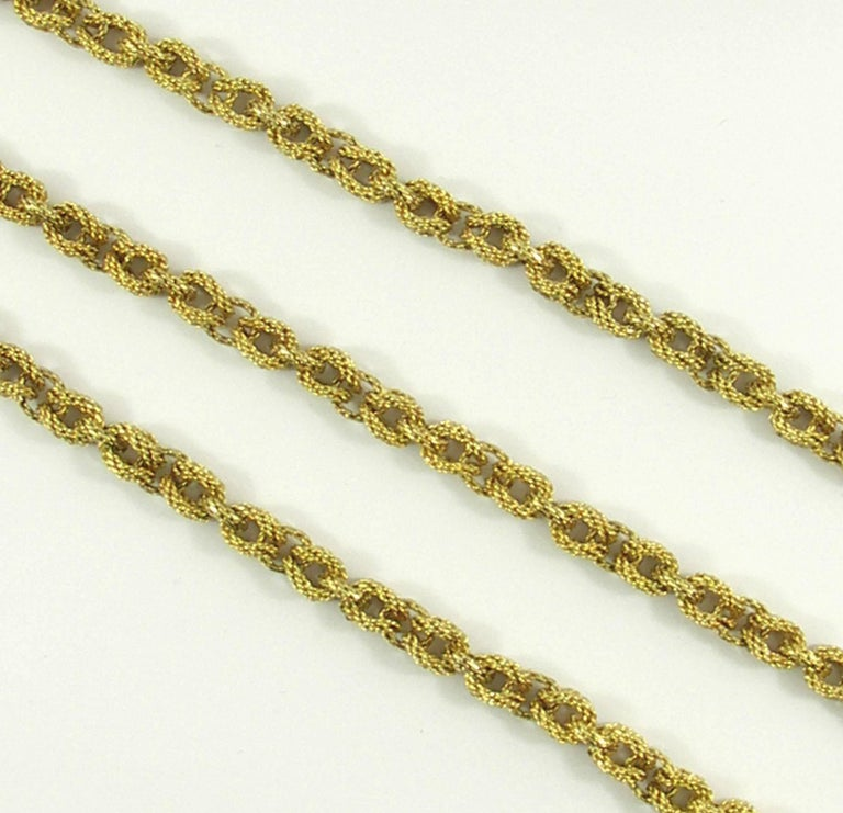 An 18K yellow gold necklace measuring 36 inches long, comprised of alternating lark's head loops, and connectors. Measuring 1/4 inch wide the three dimensional links, combined with the texture create a rich look. Signed Tiffany & Co., the overall