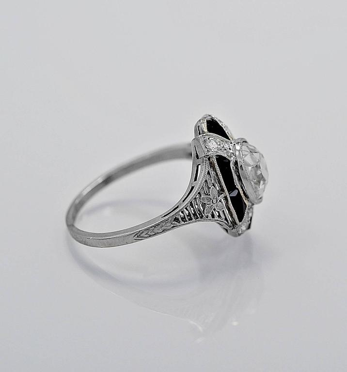 An extraordinarily unique antique engagement ring - fashion ring featuring a 1.10ct. apx. cushion cut diamond accented artistically with fancy cut onyx. It is also finely pierced, engraved & accompanied by a flower east to west on top of the