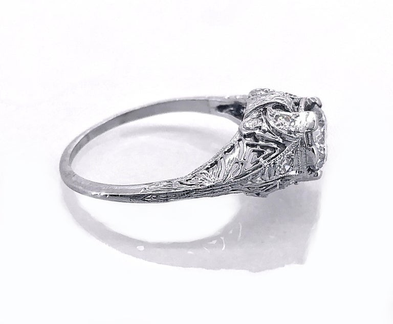 An Edwardian platinum and diamond Antique engagement ring featuring a .94ct. apx. diamond center of SI2 clarity and J color. This ring exhibits intricate filigree and .20ct. apx. T.W. of accenting diamonds. The complimenting diamond and meticulous