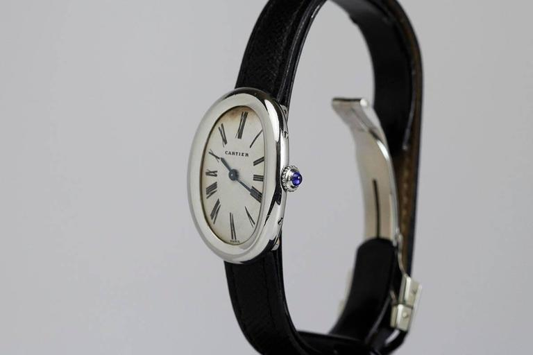 Classic Cartier Baignoire lady's wristwatch with an original dial, Roman numerals, blued steel hands, curved oval platinum case with hidden lugs on a leather strap and deployant Cartier clasp.  According to today's fashion we would consider this
