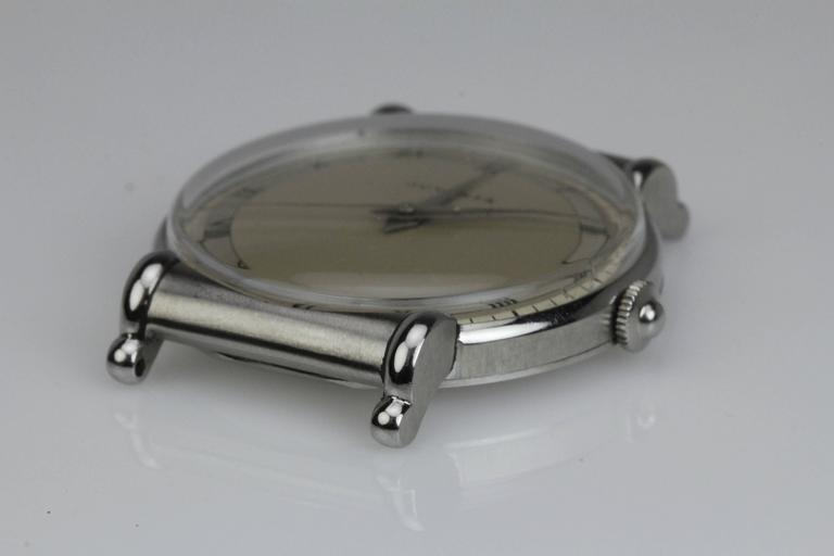 This is an elegant Calatrava style wristwatch by Juvenia from the 1940's. The 33mm stainless steel case has  partially hooded scroll lugs. This is a manual wind movement