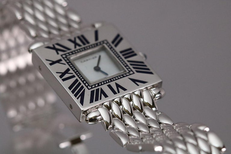Cartier Quadrant square 18k white gold case on a white gold bracelet with enamel numerals. This has the Piaget movement and is on a white gold Cartier bracelet with fold over deployant clasp.