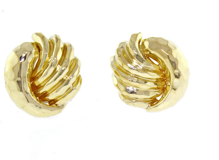 From award winning designer Henry Dunay, a a pair of 18 karat gold earrings. The earring feature Dunay's signature hammerers finish. 23 grams  22mm X 21mm clip backs, post maybe added id desires