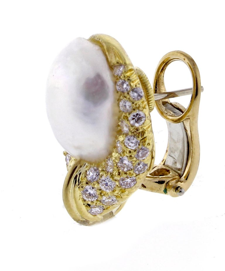 From Henry Dunay this stunning pair of pearl and diamond earrings.  The 18 karat gold earrings are comprised of 50 brilliant diamonds weighing approximately .90 carats and features a baroque cultured pearls measuring 13 x 10mm. Overall earrings 21 x