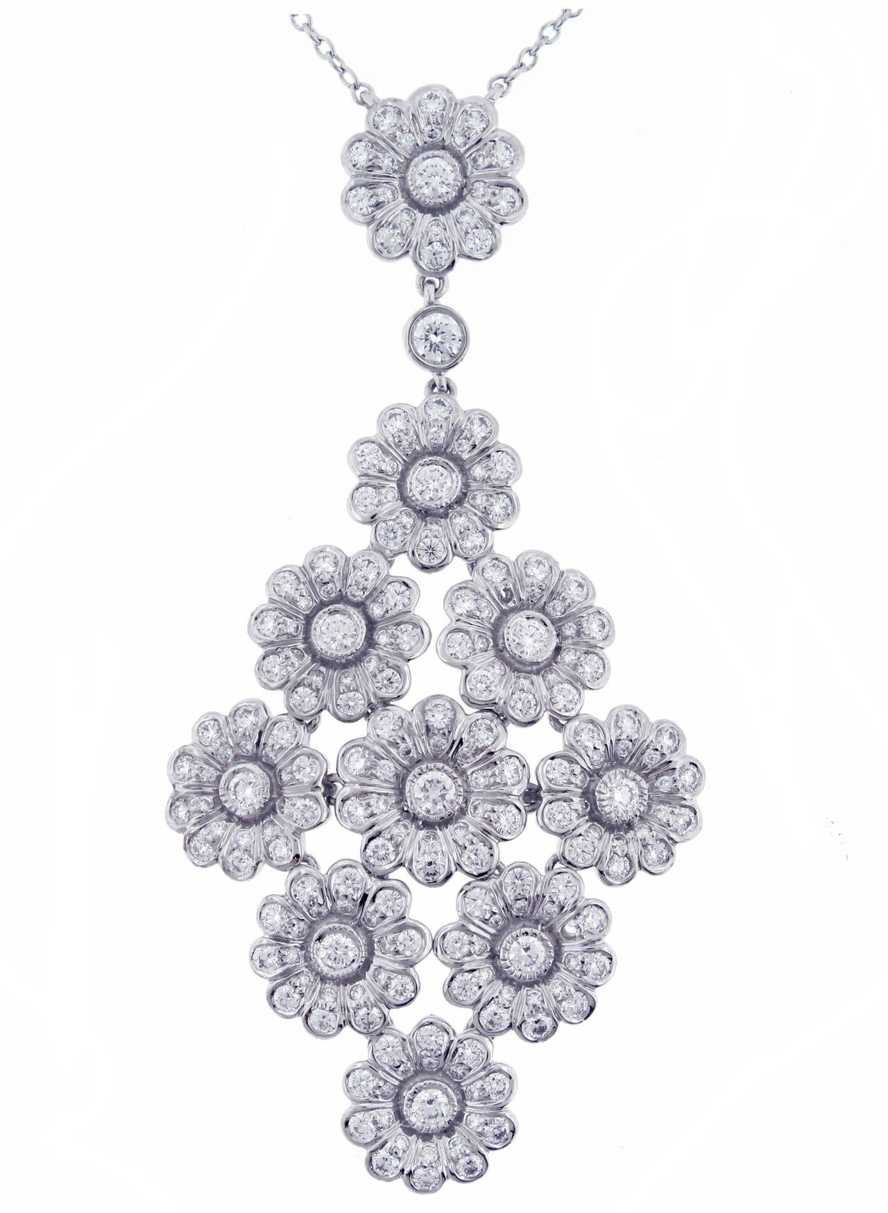 This platinum diamond drop necklace is comprised of a nine flower motif drop on a diamond necklace. Each rose motif is individually hinged for flexibility. Set with 219 shimmering diamonds weighing approximately 2.1 carats, F-G color and VVS