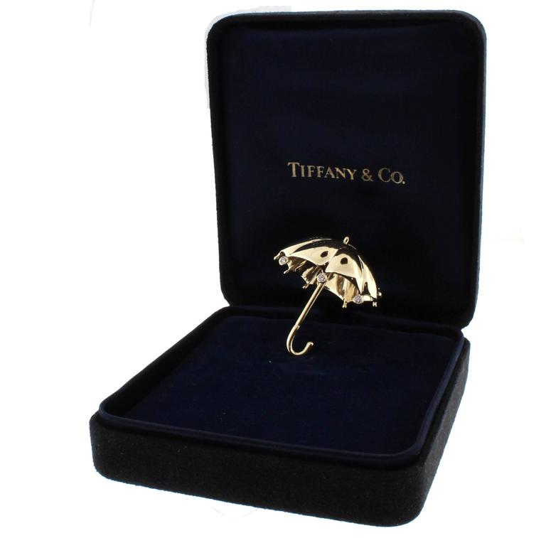 A whimsical umbrella brooch from Tiffany and Co. Set with three diamond rain drops this is the perfect accessory for a rainy day. This 18 karat brooch is in exceptional condition with no scratches or any signs of wear in it's original box.