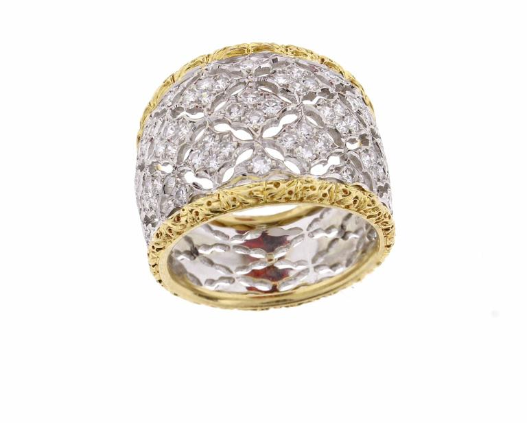 Federico Buccellati ring in 18 Karat yellow and white gold.  This wide diamond ring features white gold filigree set with sixty two brilliant cut diamonds weighing .60 carats edged with yellow gold filigree. The ring tapers from 16mm to 10mm 8.4