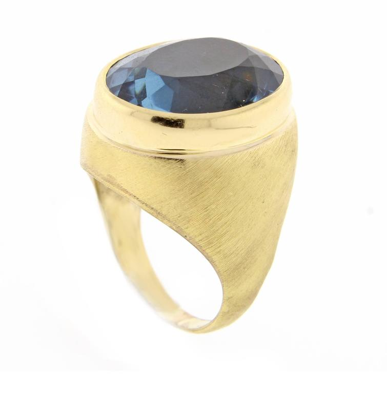 Impressive oval blue topaz ring by renowned Brazilian jeweler Haroldo Burle Marx (1911-1991). The ring features a bezel 18*14.5mm oval rich blue topaz weighing 17 carats set in a brushed 18 karat gold setting. Size 6 adjustable
