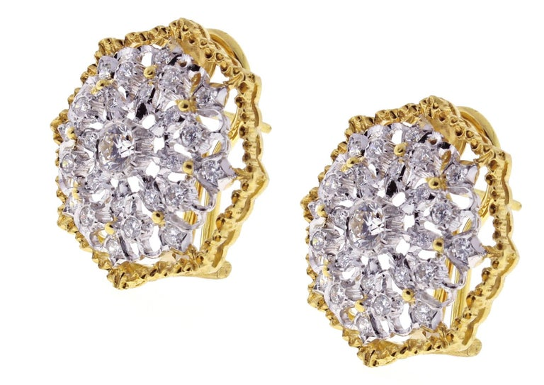 Designed of hand pierced open work and diamonds these white and yellow 18 karat gold earrings by Mario Buccellati exemplify the highest level of Italian craftsmanship. The two center diamonds weigh approximately .60 carats and the 48 round diamonds