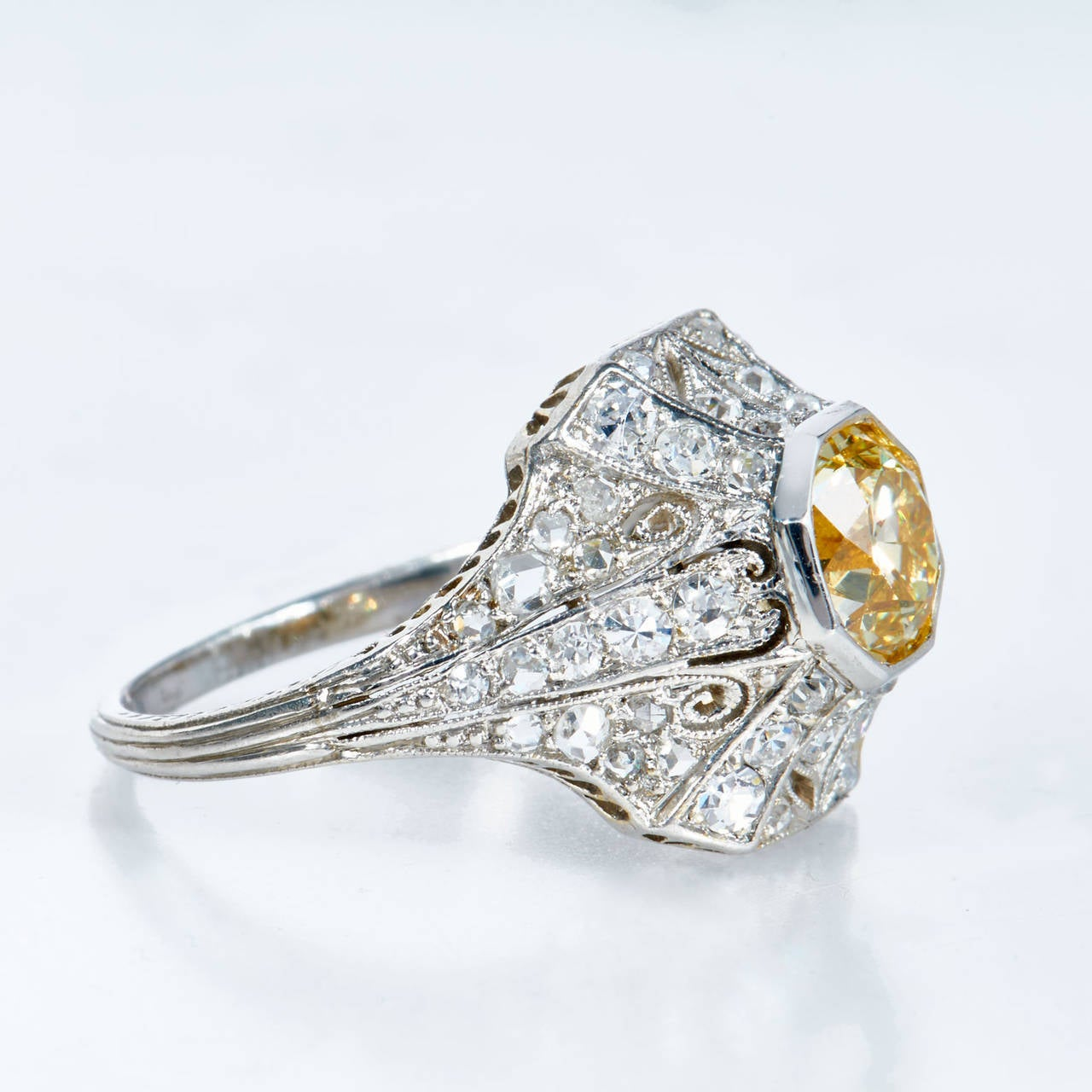 This dazzling Art Deco ring, features a sensational, natural fancy yellow old European-cut diamond weighing 1.25 carats. GIA graded, this natural diamond with VVS2 clarity shines from atop a gorgeous, original Art Deco mounting. Natural fancy yellow