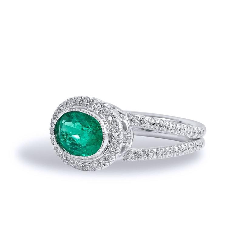 18kt white palladium forms the base for this luscious handmade Emerald and Diamond ring. Taking center stage is a 1.84 carat oval cut Zambian Emerald displaying a vivid green hue. Clutching the center gemstone and trailing down the split shank are