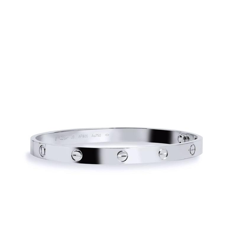 Effortlessly integrating strength and elegance, this bangle is a part of Cartier's famous LOVE collection. This piece is crafted in 18kt white gold and features Cartier's iconic screw motifs. It's in excellent condition and comes with original