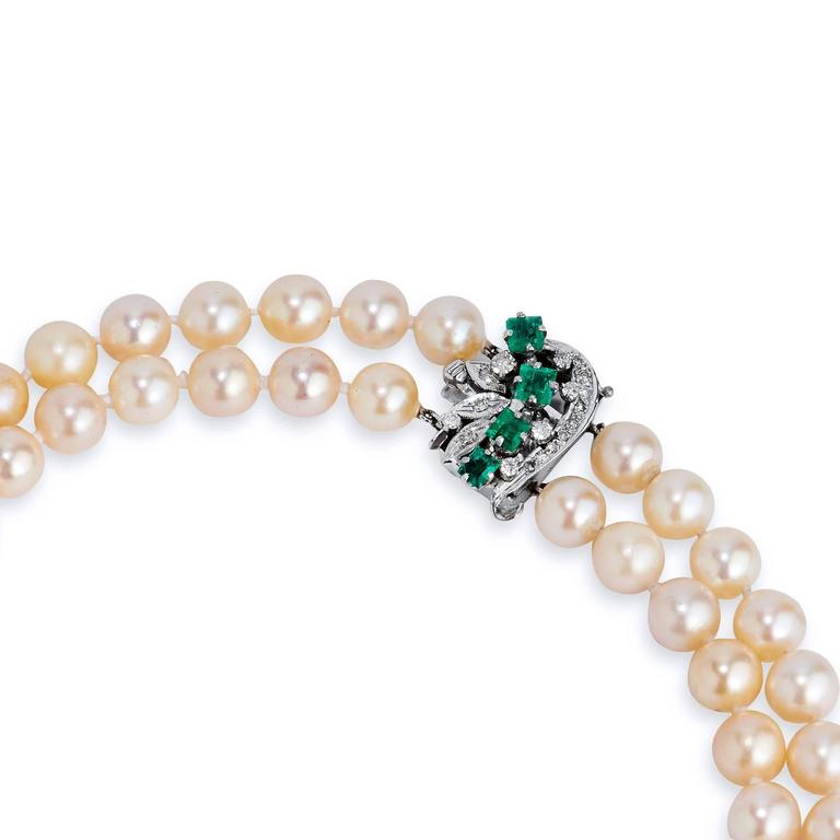 Crafted in 18kt white gold, this necklace is composed of Akoya Pearls measuring 7.5mm-8mm set in a beautiful double strand design. The clasp features approximately 1.50ct of Colombian Emeralds sprinkled with  approximately .25cts of single cut