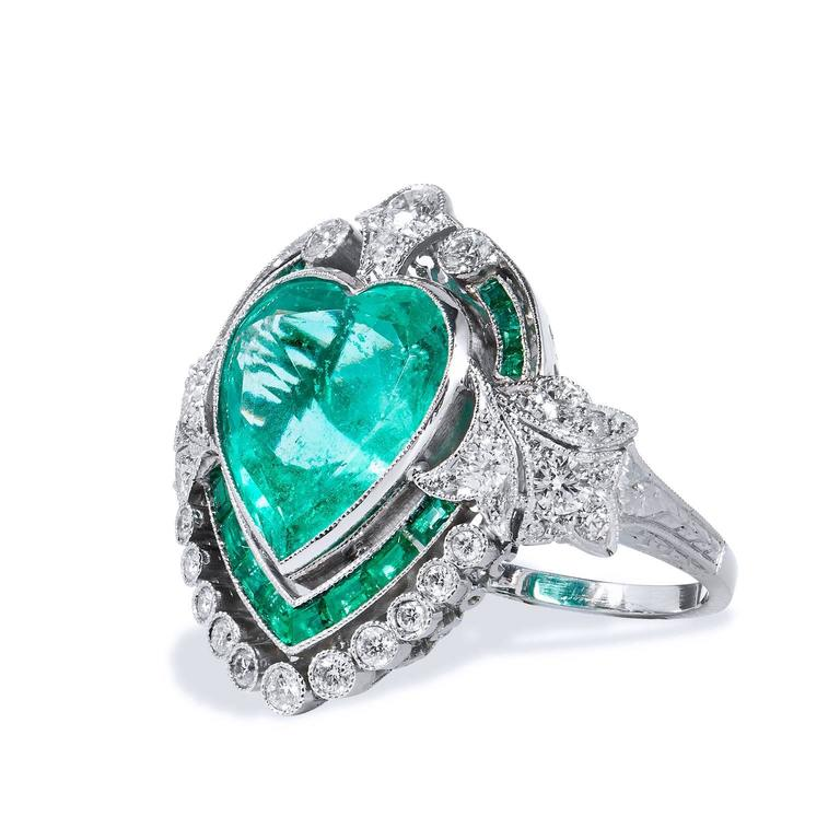 Crafted in platinum, this Art Deco style ring chants true love and uniqueness. The piece features a stunning 5.87ct Colombian heart shape Emerald surrounded by 1.03ct of additional emeralds. Ornate filigree and .85ct of G/H SI2 graded diamonds