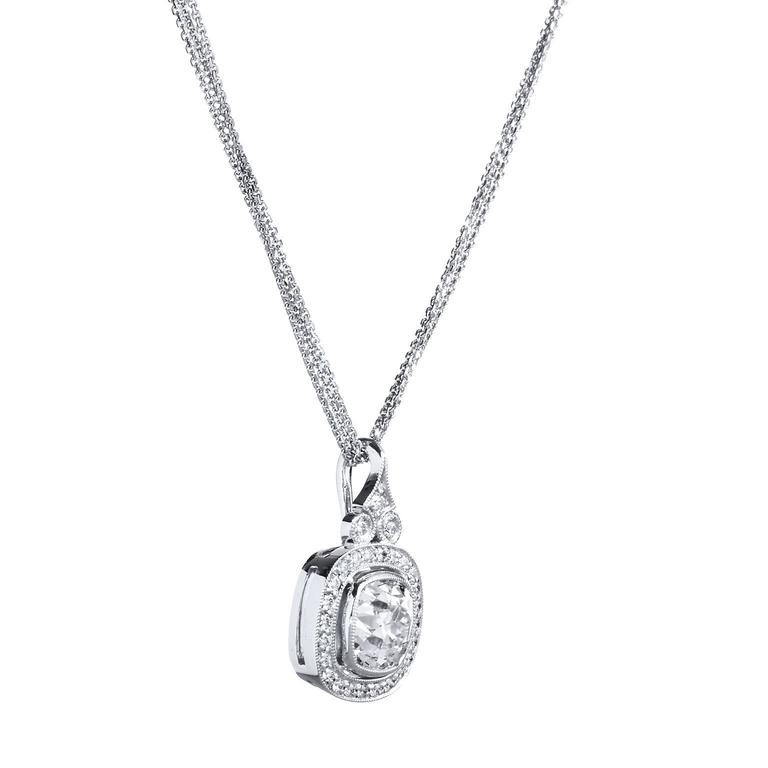Bezel set, a fascinating cushion shaped old mine cut 2.30ct K-VS diamond snuggles amongst a 0.24ct K/L VS diamond pave setting that runs around its voluptuous contour. Three diamonds charm the top of the piece, two in their very own 18kt white gold