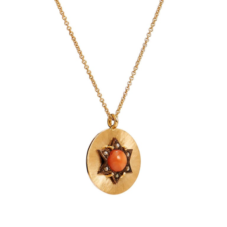 Enjoy this previously loved Victorian era coral and seed pearl pendant necklace fashioned in 18 karat yellow gold.