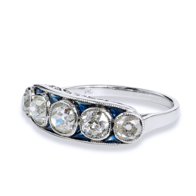 This platinum diamond band ring features five pieces of old mine cut diamonds, bezel set, with a total weight of 2.15 carat. Interlaced between the sea of diamonds are 8 pieces of trillion cut blue sapphire, with a total weight of 0.60 carat- adding