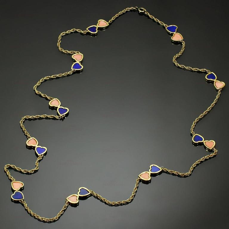 "This rare and fabulous Van Cleef & Arpels necklace is crafted in 18k yellow gold and accented with romantic double-heart motifs set with pink coral and lapis lazuli. Made in France circa 1960s. Measurements: 0.38"" (10mm) width, 30"""