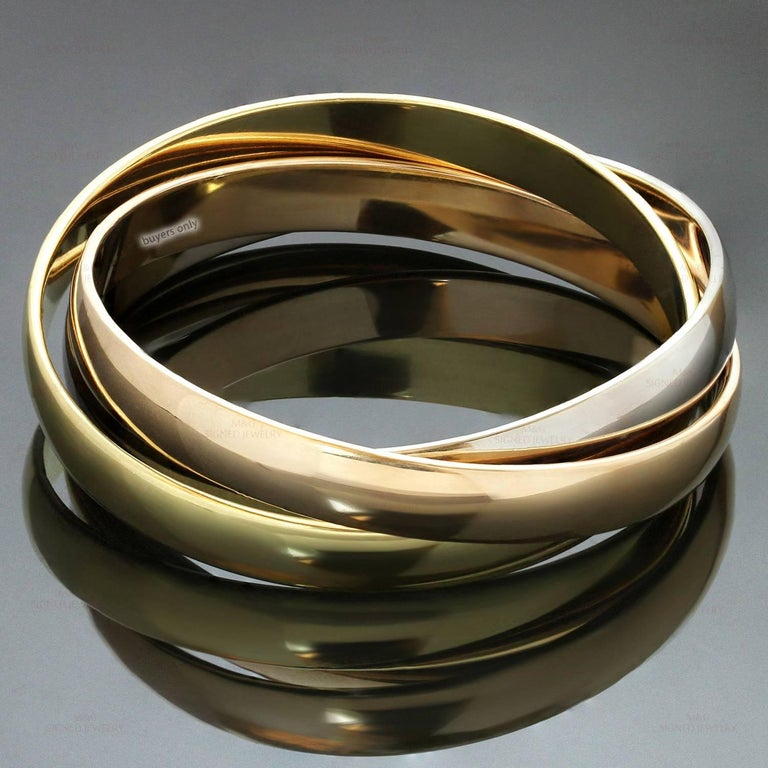 This iconic bracelet from Cartier's Trinity collection features 3 interconnected bangles crafted in 18k yellow, white, and rose gold. Made in France circa 1980s. Measurements: 0.35