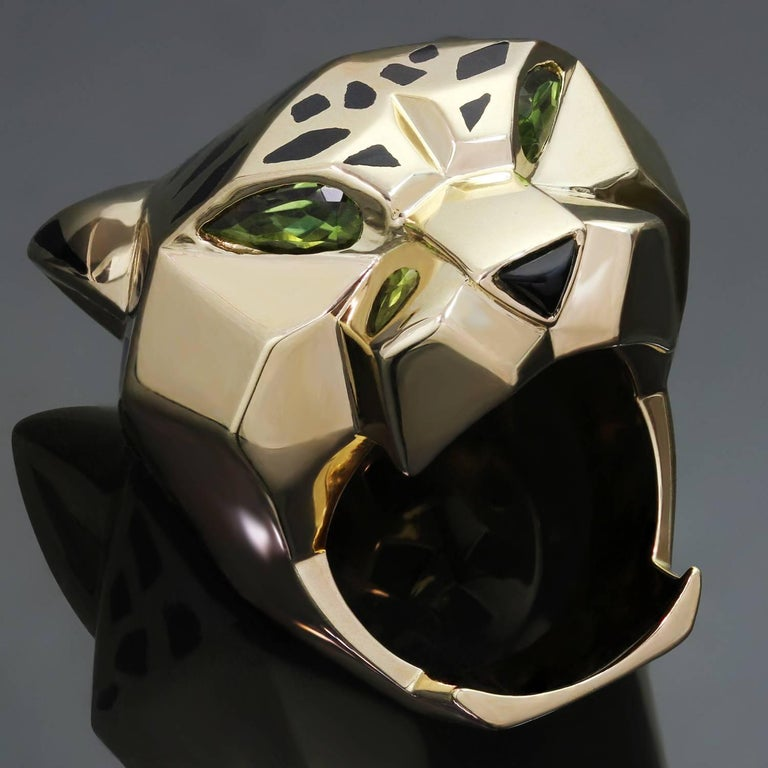 This gorgeous Panthère de Cartier ring features a chic and fierce panther design crafted in 18k yellow gold with black lacquer spots, faceted peridot eyes and a black onyx nose. Made in France circa 2010s. Measurements: 1.22