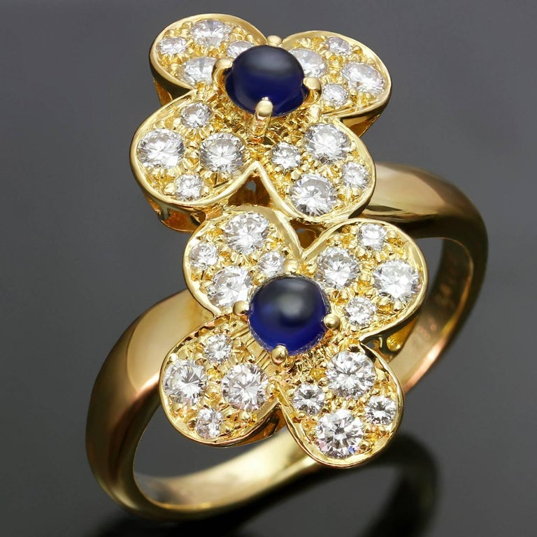 This stunning Van Cleefs & Arpels ring from the classic Trefle collection is crafted in 18k yellow gold and features a double clover flower motif set with round cabochon sapphire of an estimated 0.65 carats and brilliant-cut round diamonds of 0.80