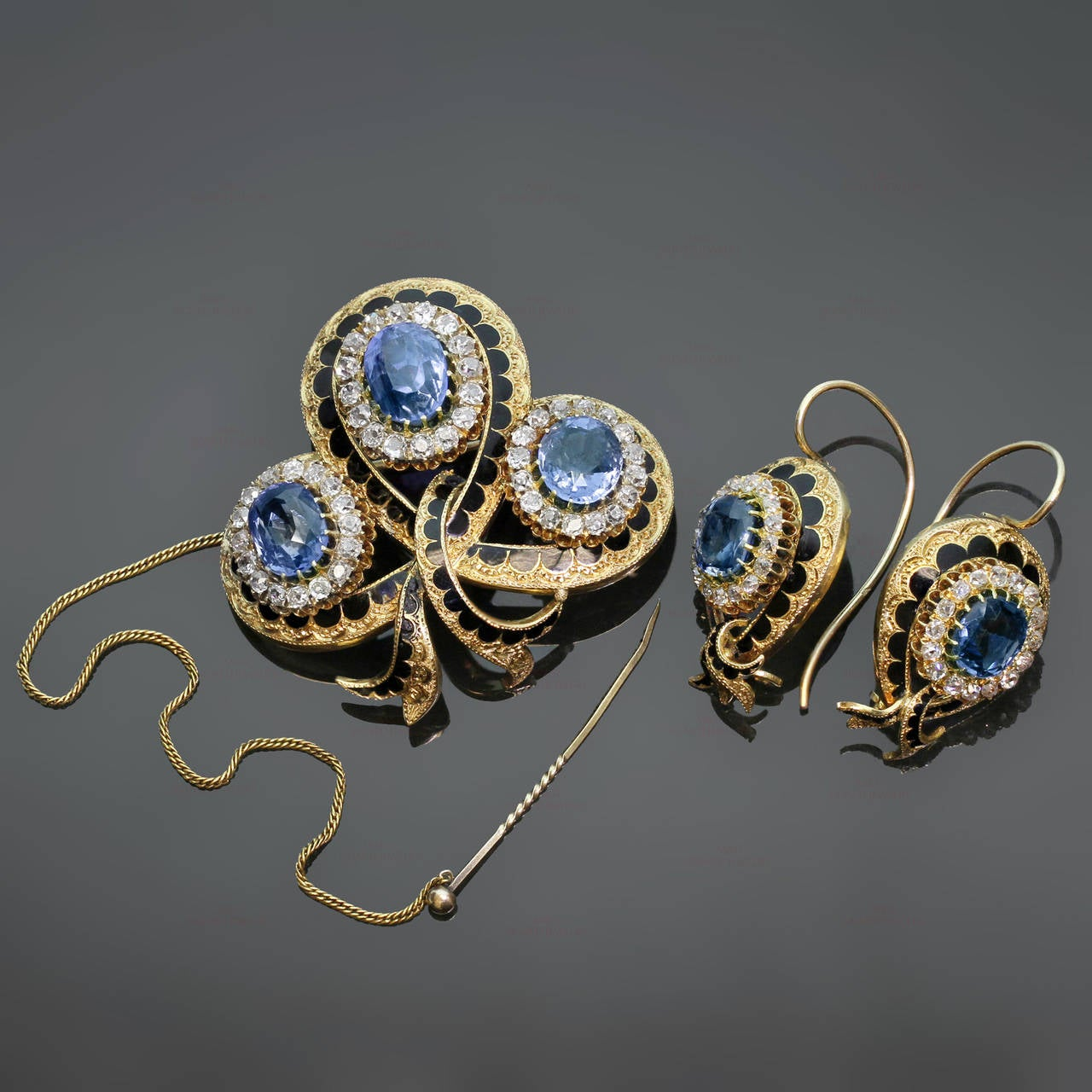 This magnificent Victorian jewelry suite consists of a pendant-brooch and a pair of earrings featuring an intricate filigree design hand-crafted in 18k yellow gold and contrasted with black enamel. This suite is beautifully prong-set with natural