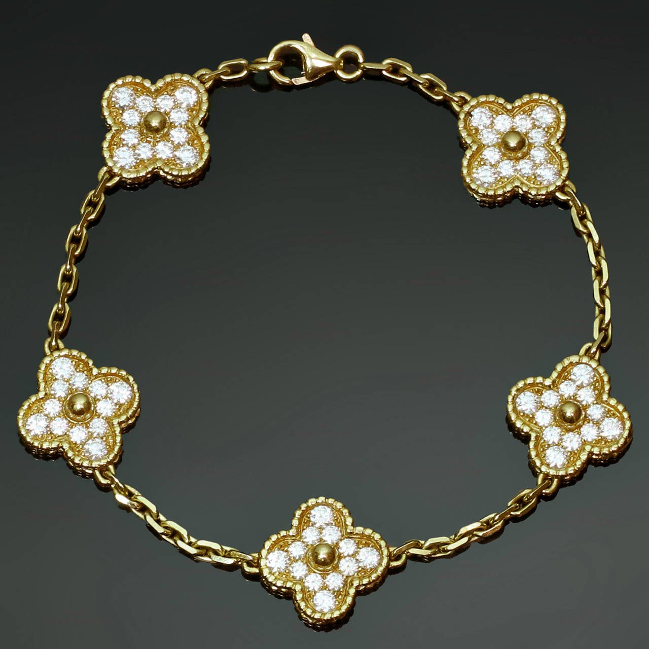 This classic Van Cleef & Arpels Alhambra bracelet features 5 lucky clover charms crafted in 18k yellow gold and set with brilliant-cut round diamonds of an estimated 1.80 carats. Measurements: 0.55