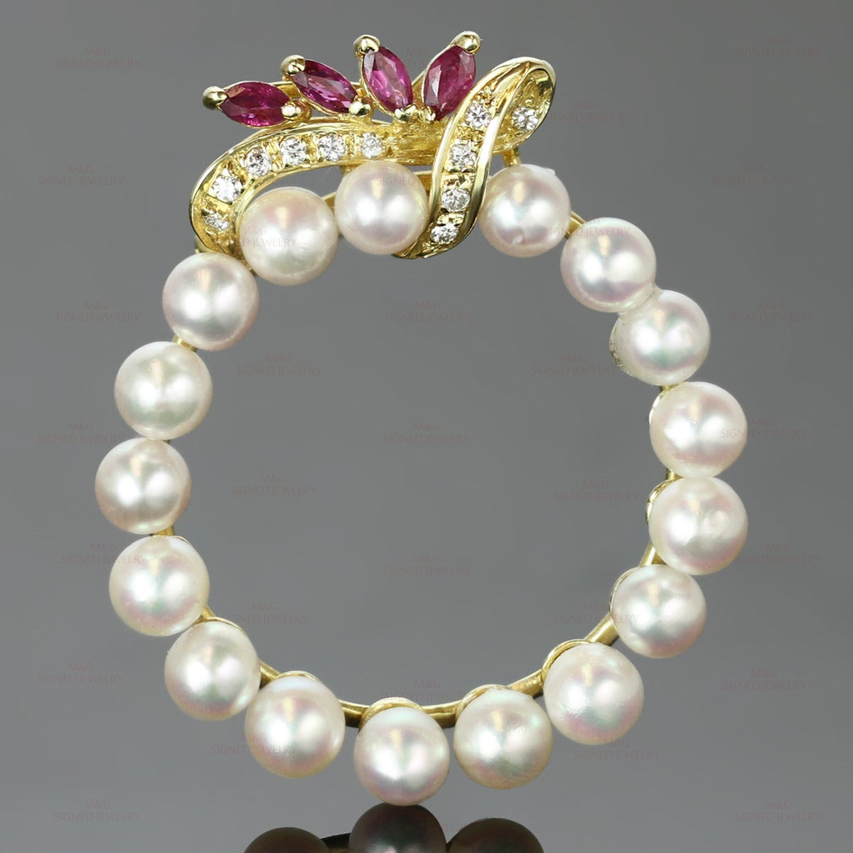 This elegant vintage brooch features a classic round design made in 14k yellow gold and cultured pearls accented with brilliant-cut round H-I VS2-SI1 diamonds of an estimated 0.10 carats and 4 marquise-cut faceted red rubies of an estimated 0.24