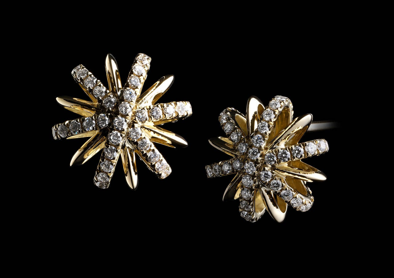 A pair of 10mm Diamond snowflake stud earrings detailed with Alexandra Mor's signature 1mm floating Diamond melee bands and knife-edged wire. Earrings are set in 18 karat yellow gold and feature 100 round diamonds with a total diamond weight of 0.34