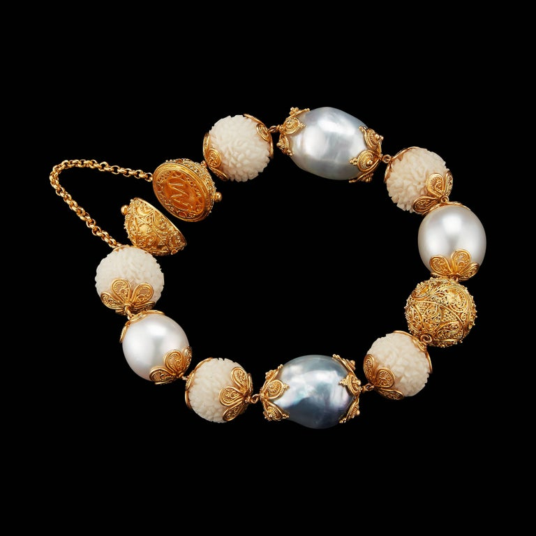 This bracelet features wild-harvested carved Tagua Rudraksha Beads, Baroque pearls and yellow gold filigree spheres set in 22 karat yellow gold with Alexandra Mor logo clasp. Prolific, internal carvings in 22 karat yellow gold are inspired by the