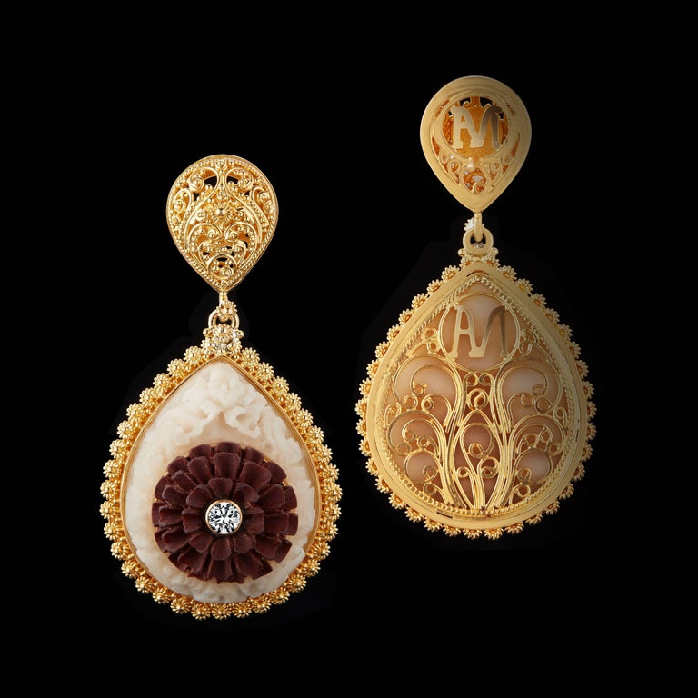 These teardrop earrings feature Balinese design motifs of the Kayonan, or Tree of Life, in carved Tagua and Lotus flowers in carved Sawo wood, accented by two Brilliant-cut Diamonds weighing .11 carats total. Prolific carvings in 22 karat yellow are