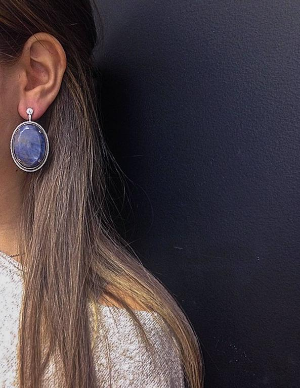 *Please contact us for more information on this piece or on creating your own Alexandra Mor custom Design.   A pair of Alexandra Mor dangling earrings featuring 74.38 carat oval Sapphire and Diamonds. Sliced Sapphires are connected to round Diamonds