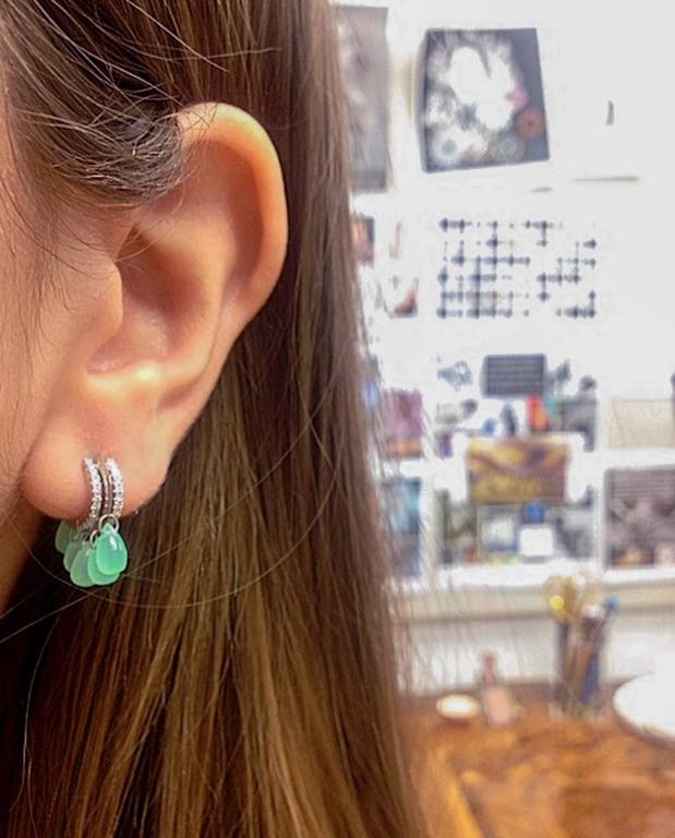 A pair of Alexandra Mor close-fitting Diamond hoop earrings featuring ten Green Chrysoprase Briolettes accented with Alexandra Mor's signature floating Diamond melee and knife-edged wire. Total Chrysoprase weight is 5.88 carats. Hoops feature 92